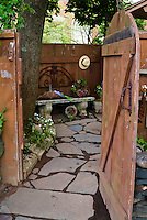 Dress up a rustic fence with rustic ornaments, open door inviting into secret secluded charming garden with flagstone path walkway and bench