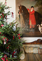 A Christmas tree decorated with red bows in the living room next to an equestrian painting