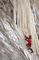 An ice climber works his way up a slab of ice hanging off a cliff on the bluff above Cook Inlet near Ninilchik, Alaska. The extreme winter sport is well-suited to the area.
