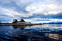 Blackfish Sound islet shimmers in evening light as a storm passes, near Stubbs Island, Broughton Strait, and Telegraph Cove on Vancouver Island, Canada.  Kayakers camp.