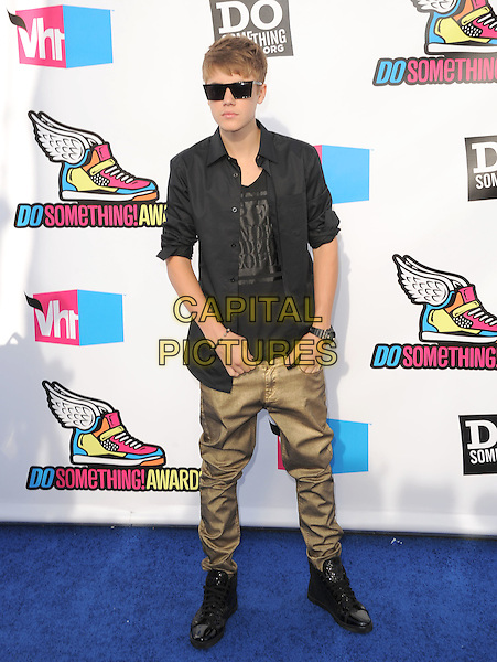 Justin Bieber.The 2011 Do Something Awards held at The Palladium in Hollywood, California, USA..August 14th, 2011.full length black jacket sunglasses shades top brown khaki gold jeans denim hands in pockets                                                    .CAP/RKE/DVS.©DVS/RockinExposures/Capital Pictures.