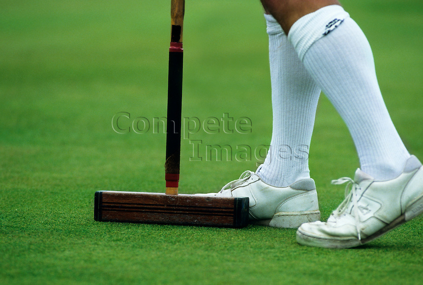 Croquet player with a croquet mallet by his feet