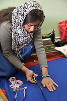Dehradun,  India.  Indian Muslim woman cutting cloth after measuring with tape measure.