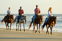 A group of people ride horses along the beach at sunrise in Amelia Island, FL