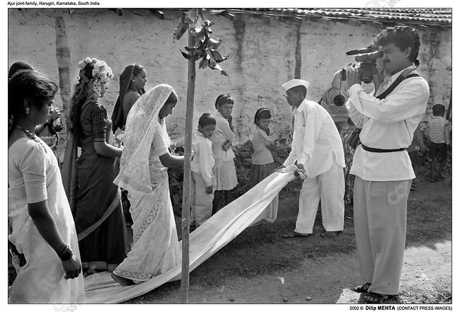 Prior to the wedding, Dr. Kumar's sister, with flowers on her head, leads a procession (followed by Dr. Kumar who is not in the frame) around the house and to the family temple and back. The video camera is a must. The cameraman is hired from the town of Harugiri.