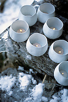 Tealights in delicate porcelain holders have been placed on the ice-covered wooden outside steps to the barn