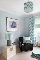 A child's bedroom furnished with matching zig-zag lampshades in green tones