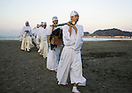 A box filled with seaweed is carried by priests on the sands of Yuhigahama beach as they make their way back to the Tsurugaoka Hachimangu shrine grounds 2 km away during a purification ritual known as hamaorisai at the start of the 3-day Reitaisai festival in Kamakura, Japan on  14 Sept. 2012.  As a symbol of the purification, priests collect the seaweed from the sea and take it back to the shrine, hanging pieces around the shrine grounds to appease the gods. Photographer: Robert Gilhooly
