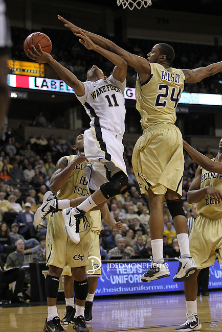 Wake Forest Demon Deacons guard C.J. Harris (11) leaps for a score as Georgia Tech Yellow Jackets forward Kammeon Holsey (24) and Georgia Tech Yellow Jackets guard Lance Storrs (10) try for the block. Georgia Tech leads at the half 35-28.