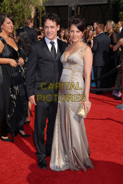 T.R. KNIGHT & GUEST.59th Annual Primetime Emmy Awards held at the Shrine Auditorium, Los Angeles, California, USA..September 16th, 2007.full length black suit purple grey gray dress gold clutch purse .CAP/ADM/BP.©Byron Purvis/AdMedia/Capital Pictures.