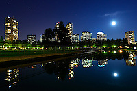 Leading line to a full moon rising over a city Skyline, Park and Reflecting Pool. Bellevue, Washington.