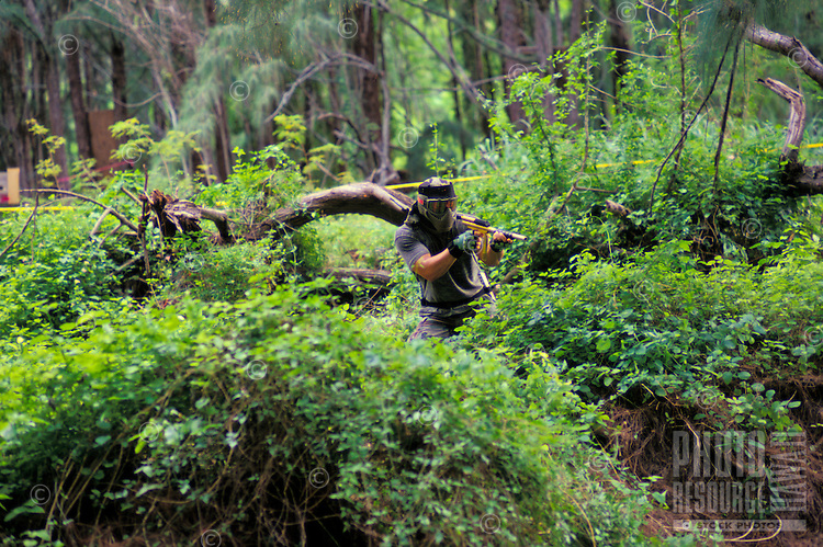 Man engaged in paintball sport, a paramilitary leisure type game, Kualoa Ranch