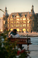 Romantic Turkish couple at dusk with Haydarpasa train statio in the background, Istanbul, Turkey