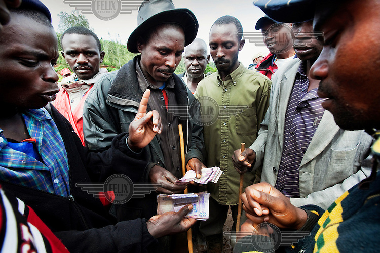 A dealer pays a farmer for his animals at the Rurangazi animal market.