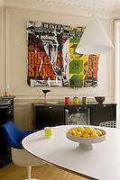 "In the kitchen/dining room the chairs surrounding the large dining table are antique Bertoia and Knoll designs and the collage above the sideboard is a work entitled ""Rolilng Stones VI"" by artist Raymond Hains"