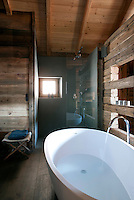 A contemporary free-standing bath contrasts with the rustic larch-covered walls in this chalet bathroom