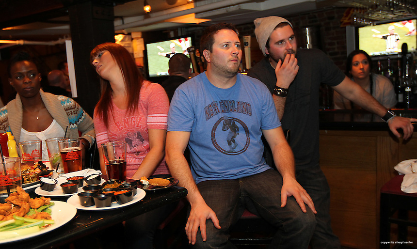 Portsmouth residents, from left, Jenaya Butler, Erica Madden, Joe Kelley, (owner of Fat Belly's), and, Shane Emerson, watch the Super Bowl in Fat Bellyy's in Portsmouth, N.H., Sunday, Feb. 5, 2012.  (Portsmouth Herald Photo Cheryl Senter)