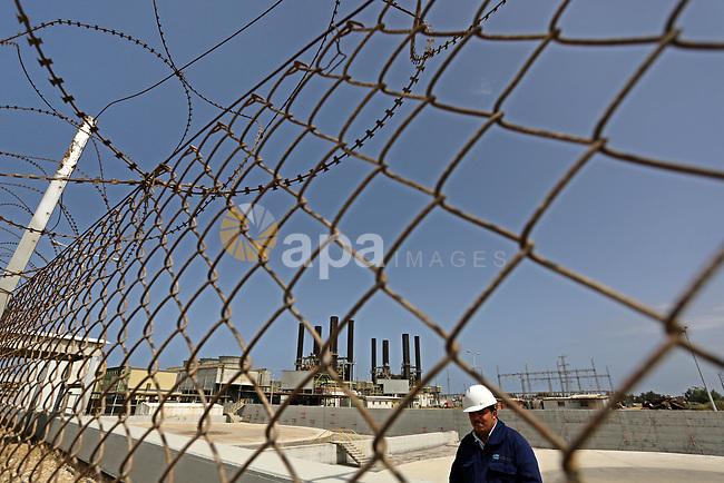 A Palestinian worker stands near the fence of the power plant during a protest calling for an end to the power crisis, in the central Gaza Strip April 23, 2017. Photo by Ashraf Amra
