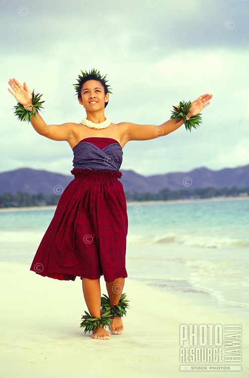 Young woman dancing hula on the beach wearing kupee on wrists and ankles and shell necklace
