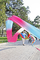 Woman swirling colorful silk scarves, Temple of Heaven Park, Beijing, China, Asia