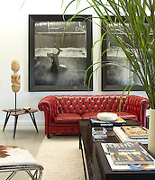 In the living room a pair of Steven Klein photographs is displayed above a lipstick-red Chesterfield sofa