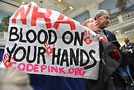 December 21, 2012  (Washington, DC)  Codepink.org protester Madea Benjamin holds a sign and is led away as she interrupts NRA President Wayne Lapierre during a news conference in Washington.  (Photo by Don Baxter/Media Images International)