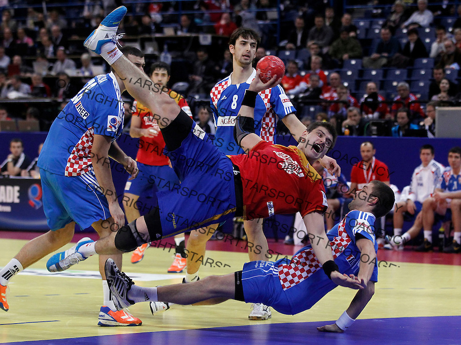 BELGRADE, SERBIA - JANUARY 29: Julen Aguinagalde (TOP) of  Spain jumps to score past Drago Vukovic (DOWN) of Croatia during the Men's European Handball Championship 2012 Bronze medal match between Croatia and Spain at Arena Hall on January 29, 2012 in Belgrade, Serbia. (Photo by Srdjan Stevanovic/Starsportphoto.com ©)