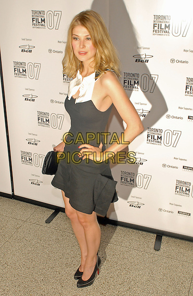 "ROSAMUND PIKE.""Atonement"" North American Premiere Screening duringthe Toronto International Film Festival 2007 held at Elgin Theatre, Toronto, Ontario, USA,.10 September 2007..full length black dress white bow hand on hip shoes clutch bag.CAP/ADM/BP.©Brent Perniac/AdMedia/Capital Pictures."