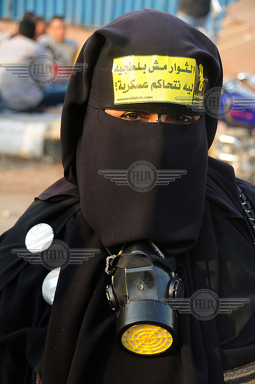 A veiled woman wears a gas mask as protesters gather in Tahrir Square for a rally demanding an immediate transfer of power from Egypt's military rulers SCAF (Supreme Council of the Armed Forces) ahead of the elections taking place on 28 November.