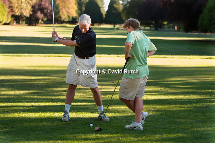 Father giving son golfing lessons