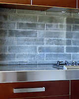 The glass-covered brick splashback shows a clever use of materials - the brick provides texture and the glass ensures easy maintenance