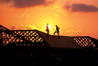 Carpenters in silhouette at sunset on top of a new home construction.