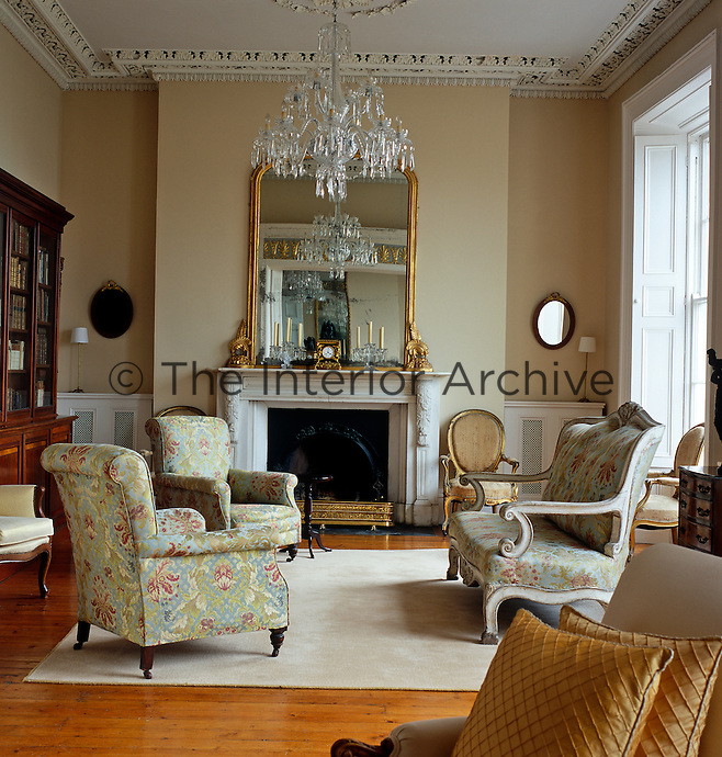 This drawing room has retained the ornate cornice and ceiling plasterwork together with a grand fireplace original to its period and is furnished with a combination of antiques