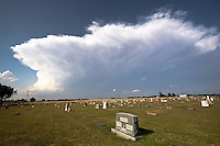 Sheared anvil thunderstorm cloud behind tombstones in a cemetery in Watonga, OK, May 29, 2012