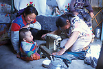 Sewing clothes  inside  a Ger in outer Mongolia.  Tsataan Uul.