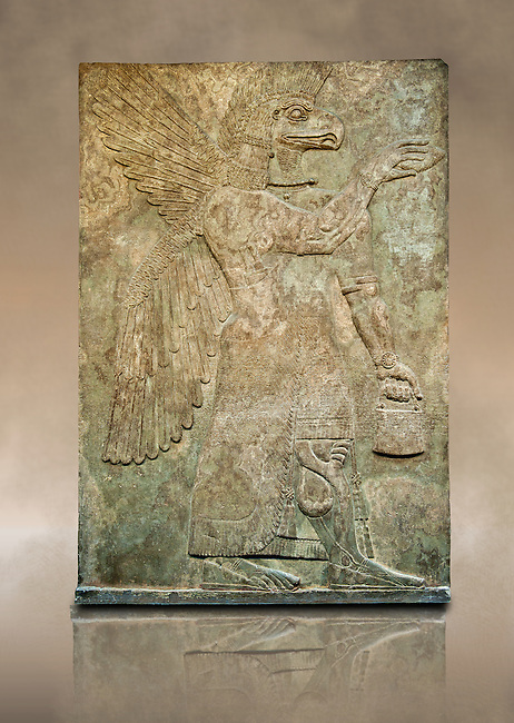 Assyrian relief sculpture panel of a protective spirit with an eagles Head from Nimrud, Iraq.  The spirit is holding a symbolic fir cone and is sprinkling holy water from the bucket it is holding. The rosette bracelet worn around the wrist symbolises divine power. 865-860 B.C North West Palace, Room G, panelled d1. ref: British Museum Assyrian  Archaeological exhibit WA 124576