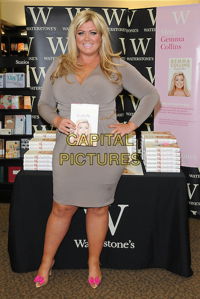 """Gemma Collins.Signs Copies Of Her New Book """"Basically...My Life As A Real Essex Girl"""" At Waterstones, The Liberty Shopping Centre, Romford, Essex, UK, 26th April 2013..TOWIE full length grey gray dress hand on hip pink shoes  bows beige peep toe long sleeve holding book .CAP/BRC.©Ben Rector/Capital Pictures."""