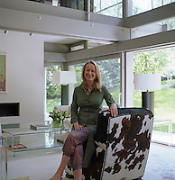 Art dealer and curator Anna Belayeva sits on a cow-hide armchair in her home