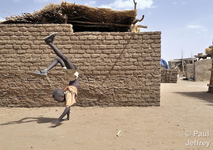 A displaced boy does a handstand in a camp outside Zalingei, in Sudan's war-torn Darfur region.