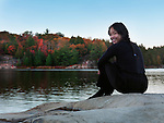 Beautiful smiling asian woman sitting on a shore of lake George, fall nature scenic, Killarney Provincial Park, Ontario, Canada.