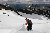 Balanced precariously, a worker pulls the blanket tight to cover Brunnenkogel Ferner (Austrian word for glacier).  It is being wrapped with a fleece-like cover to keep it from melting.  Covered ice melts slower. <br /> The ski area at 3,400 meters is covered to help save the ski industry since the glacier is retreating.