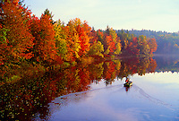 A boater takes in the scenic view of fall foliage along the Contoocook River on a misty morning. New Hampshire.