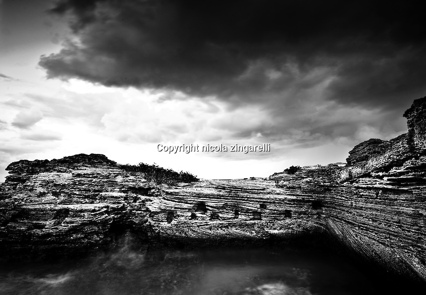 The volcanic Island of Bermuda has beautiful rock formations all around the coastline. They are black, sharp and constantly polished by the waters of the Atlantic Ocean. Stormy sky and silky waves