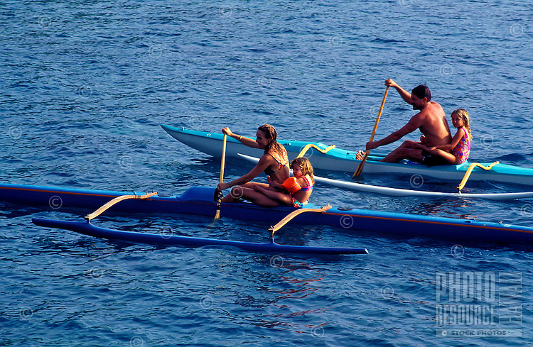 A family with two children paddle their outrigger canoes on Kealakekua Bay on the Big Island of Hawaii.