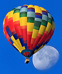 A hot air balloon piloted by Gabe Gundling of Napa Valley Balloons sails over Napa Valley, California, with the waning full moon as a backdrop.