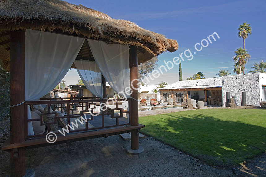 Gazebo or palapa is shown overlooking outdoor living area of backyard