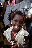 Zambia. Smiling young girl in a ragged dress with earrings.