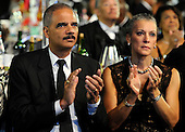 United States Attorney General Eric Holder (L) applauds along with his wife Dr. Sharon Malone as they await the arrival of U.S. President Barack Obama at the Congressional Black Caucus Foundation Annual Phoenix Awards dinner, September 21, 2013, Washington, DC. The CBC's annual conference brings together activists, politicians and business leaders to discuss public policy impacting black communities in America and abroad.  <br /> Credit: Mike Theiler / Pool via CNP