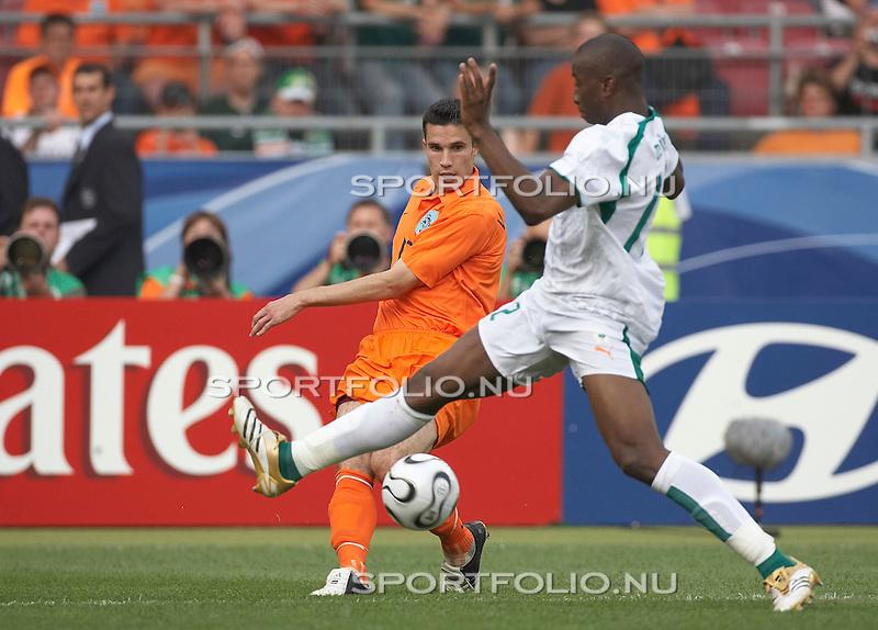 Duitsland, Stuttgart, 16 juni 2006. .WK voetbal 2006 .Groep C .Nederland-Ivoorkust (2-1). .Robin van Persie (l.) van Nederland schiet de bal door de benen van Abdoulaye Meite van Ivoorkust.