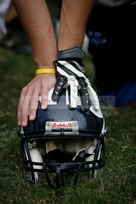 Knott County Central High School senior quarterback Braxton Ratliff and senior wide receiver Kenny Craft support themselves on helmet while listening to their coach after practice on Thursday, Sept. 17, 2009.